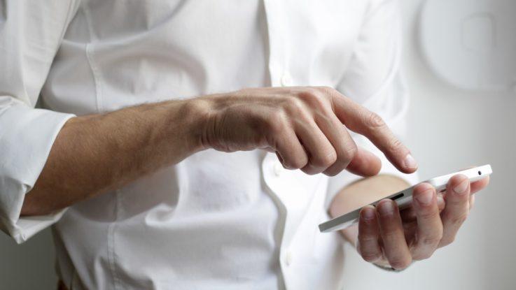Un homme manipulant son smartphone