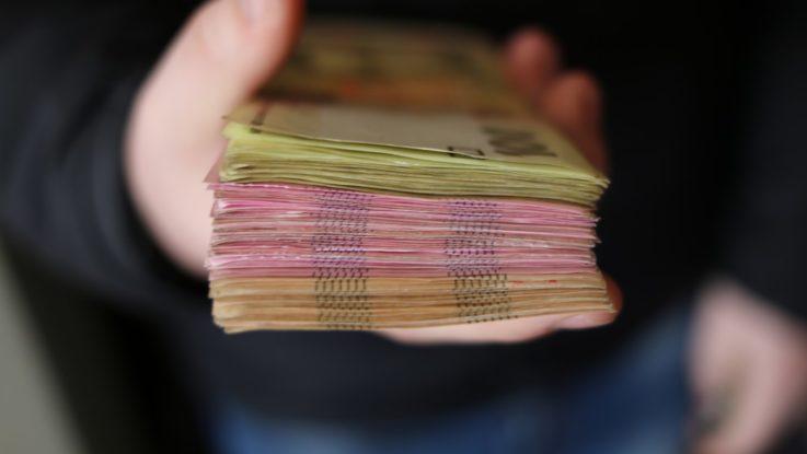 Quelqu'un tenant une liasse de billets de banques