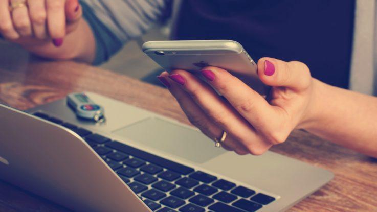 Une jeune femme manipulant un smartphone et un ordinateur.