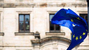 Le drapeau de l'Union européenne (UE) flottant au vent devant un bâtiment.