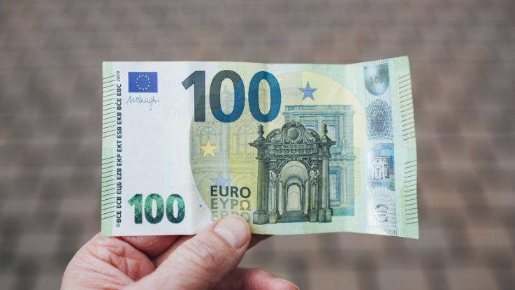 une personne avec un billet de 100 euros en main.