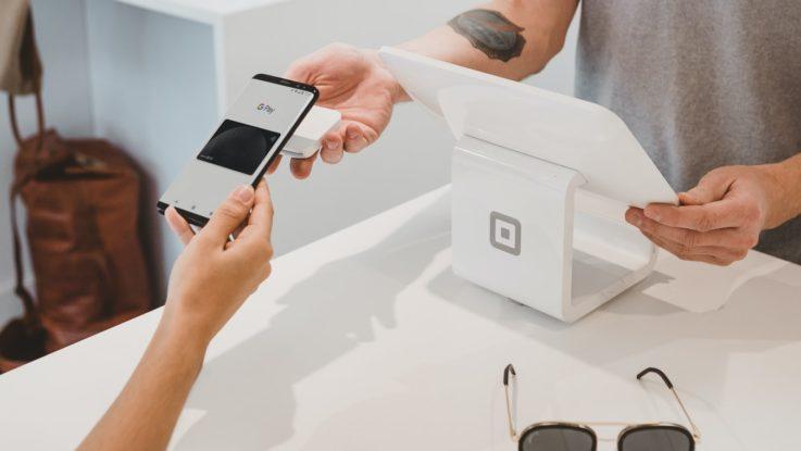 Une personne à la caisse avec un smartphone.