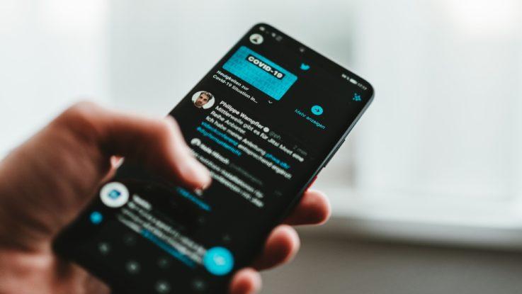 Une personne manipulant un smartphone noir qui affiche une page Twitter.