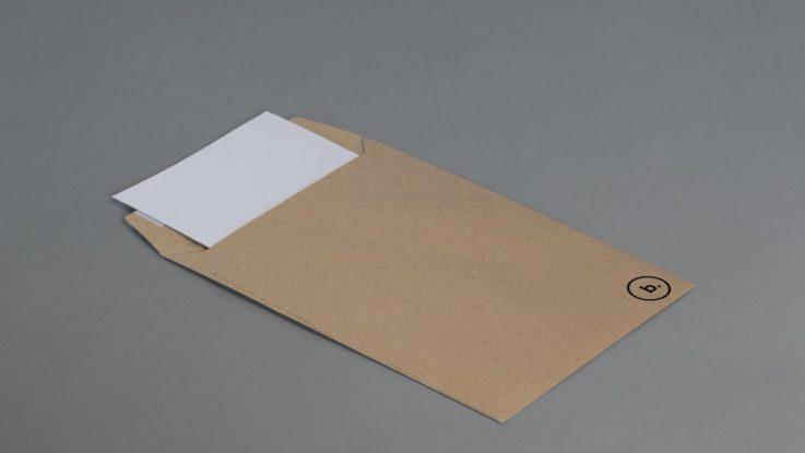 Une enveloppe kaki ouverte et posée sur une table.